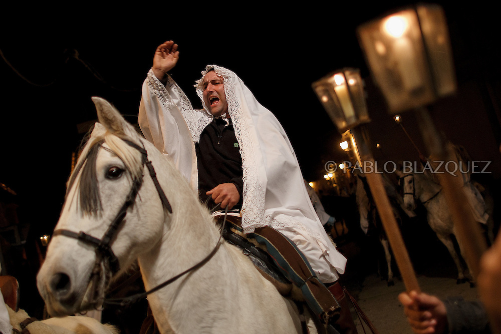 "A horseman cheer during the ""La Encamisa"" Festival on December 7,  2014 in Torrejoncillo, Extremadura region, Spain. ""La Encamisa"" is an ancient festival in honor of Immaculate Conception. Hundreds of horsemen wearing a white sheet gather outside the church in the main square. The procession starts when a banner with the image of Immaculate Conception is delivered to the horse rider steward and people cheer and shoot blanks. There are bonfires along the way where people gather to chat, eat traditional sweets and drink local wine. The origin of this tradition is unknown but it is believed the festival comes from a military event in which people from Torrejoncillo were involved. The war in Flanders in 1585, the Battle of Pavia or a legend of the siege suffered by city of Coria. (© Pablo Blazquez)"