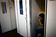 A young man uses a telephone at a telephone booth in Bilbao.Telephone booths are a common place for those arriving from abroad. They can communicate with their loved ones back at home and they can also look for jobs and housing through adverts placed in walls.