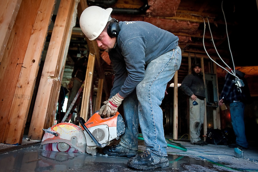 JEROME A. POLLOS/Press..Frank Zwinger, with Zwinger Excavating, cuts through concrete Wednesday while crews begin the remodel of Capone's Pub & Grill in Coeur d'Alene.