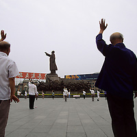 Old people exercising as a group on Zhongshan Square, dominated by a 1969 statue topped by Mao Zedong. ..From China [sur]real © Mark Henley..