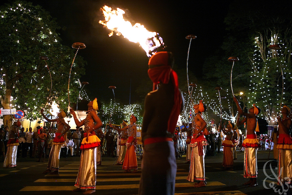 A Sri Lankan torch bearer helps illuminate performers in the Kandy Perahera outside the Temple of the Tooth (Dalada Maligawa) in Kandy, Sri Lanka August 12, 2008. The Perahera is an annual celebration in which a hundred elephants, and groups of dancers, drummers  and acrobats take part in a procession that includes a replica of the casket that contains the tooth relic..