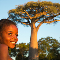 Madagascar, Kirindy Forest Reserve, Portrait of young girl and baobab tree at sunset in Tulear Province