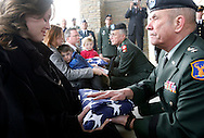 Maj. Gen. Larry Lafrenz presents a flag from the internment service for Sgt. James Holtom to Holtom's fiancé, Melissa Sewell at the Idaho Veterans Cemetery on Tuesday afternoon in Boise, ID. In the background, Maj. Gen. Lawrence Johnson presents a flag to Sgt. Holtom's father, David Holtom. Sgt. Holtom was killed in Karmah, Iraq while on a mission to rescue other fallen soldiers.