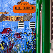 SHOT 3/17/11 8:02:22 AM - A sign for the Hotel Scharloo in Willemstad. Once thought of as the nicest, most upscale area on the island, the area of Scharloo is a compilation of beautiful old mansions some that have been completely restored and others in various states of disrepair. Willemstad is the capital city of Curaçao, an island in the southern Caribbean Sea that forms a constituent country of the Kingdom of the Netherlands. Formerly the capital of the Netherlands Antilles prior to its dissolution in 2010, it has an estimated population of 140,000. The historic centre of the city consists of two quarters: Punda and Otrobanda. The city center of Willemstad boasts an array of colonial architecture that is influenced by Dutch styles. The city center, with its peculiar architecture and beautiful harbour entry, has been made a UNESCO world heritage site. (Photo by Marc Piscotty / © 2010)