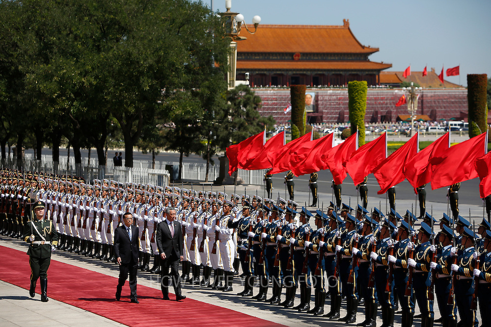 epa03837684 Singapore's Prime Minister Lee Hsien Loong (C) and Chinese Premier Li Keqiang (2-L) review honor guards during a welcome ceremony at the Great Hall of the People in Beijing, China 26 August 2013. Lee is on a seven-day visit to China where he will also visit China's Xinjiang Uygur Autonomous Region and Liaoning Province.  EPA/HOW HWEE YOUNG
