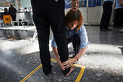 "Security employed by contractor OCS searches a passenger at Heathrow Airport's Terminal 5. Teams of 5-8 perform a rotational order of tasks, changing every 20 minutes: A loader (asking travellers to take off clothing, shoes etc); archway detectors; X-ray operator; liquid tester and bag searcher. The X-ray operator can earn a £50 bonus for a suspect item randomly inserted by undercover officials and known as an Airlock Find. Also, a Tip is a random image flashed on the screen that shows a suspect item they have to spot. A typical day of searched passengers is 25,000 passengers in T5. From writer Alain de Botton's book project ""A Week at the Airport: A Heathrow Diary"" (2009). ."