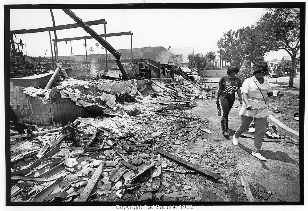 Two women walk next to a  Smart and Final store burned and looted next to USC. Vermont Ave and 36th street.