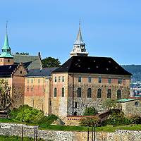 View of Akershus Fortress from Oslo Fjord in Oslo, Norway <br /> Akershus Fortress was built along the coastline of the Oslo Fjord around 1299 as a major way to defend the city against sea and land invasions. Akershus Festning successfully repelled at least six attacks by Swedish, Danish and Scottish soldiers from 1308 through the 16th century.  It only surrendered in 1940 when Germany invaded Norway during WWII.  The Germans used the big building on the right, called the Akershus National Penitentiary, as a military prison. Further on the right is the Crown Prince&rsquo;s Powder Magazine Tower (circa 1755). It was used by the Nazis as death row for Norwegian Resistance fighters. The castle was liberated in 1945. The citadel is surrounded by Crown Prince&rsquo;s Bastion, a stone wall that was finished circa 1618.