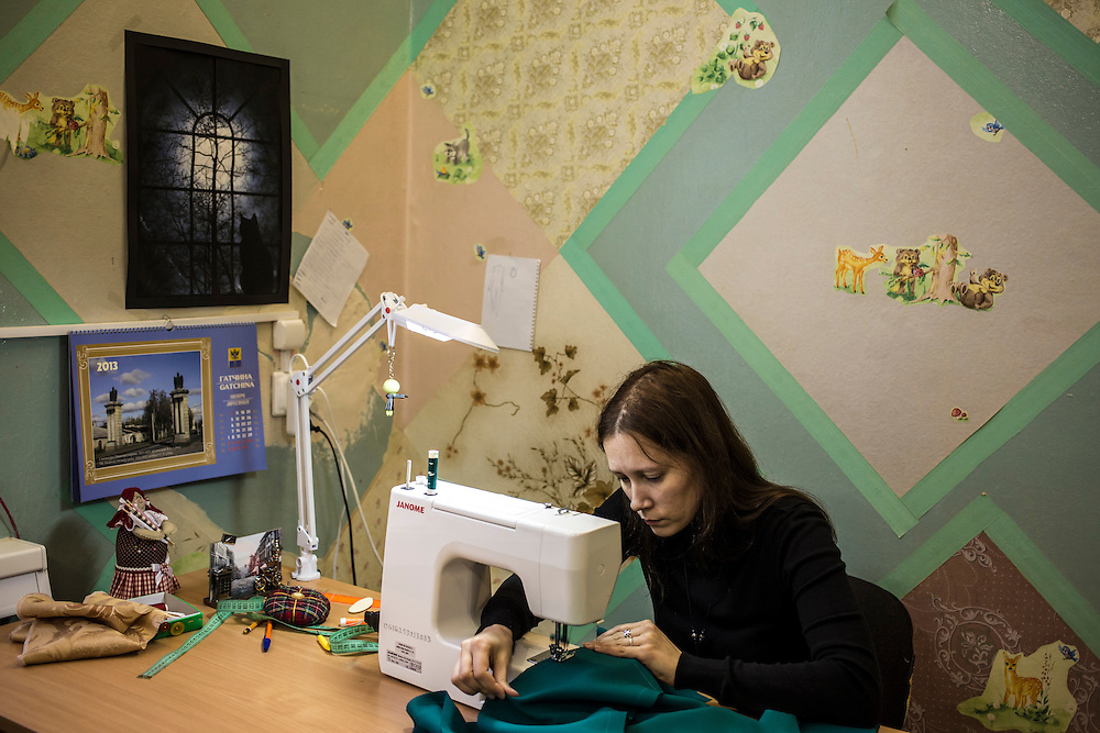 A woman sews costumes for a veterans' chorus at an arts center on Monday, November 11, 2013 in Asbest, Russia.