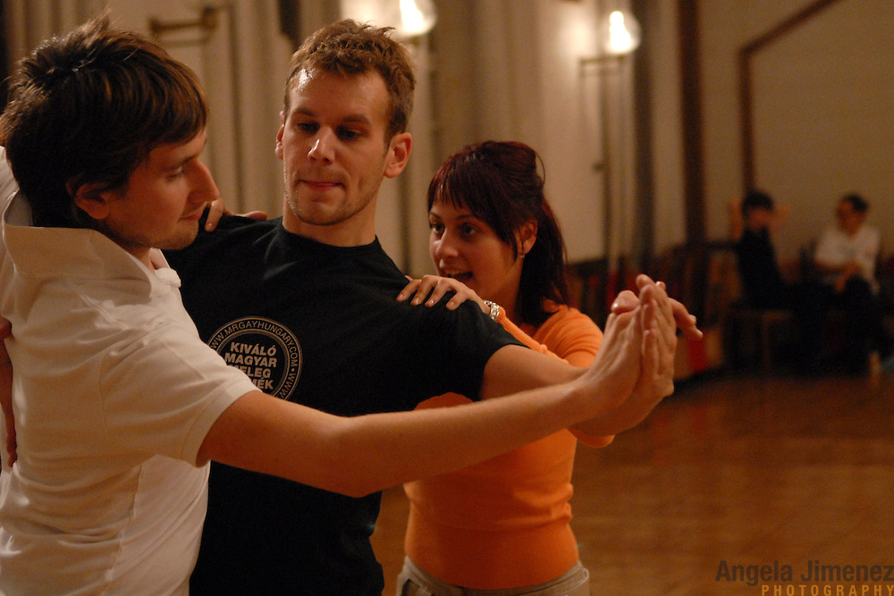 """World Champion same-sex ballroom dancers Robert Tristan Szelei, center, and Gergely Darabos, left, practice their routines with instructor Zilvia Telek, a 4th ranked.Hugarian standard dancer, at a lesson session at Leovey Klara High School in Budapest, Hungary on October 18, 2006, in preparation for the 2nd annual World Championship Same-Sex Ballroom Dancing competition, which was held in Budapest on October 21, 2006. ..This lesson session is one of the few spaces in Budapest which allows same-sex couples to train...Szelei and Darabos, who are known as the """"Black Swans,"""" are the reigning world champions in men?s Latin same-sex ballroom dancing. They have been training and preparing to host the 2nd annual World Championship and the Csardas Cup, the first-ever Eastern European same-sex ballroom competition, both held at the Korcsarnok arena.  This is the pinnacle event of the blossoming same-sex ballroom scene...Szelei and Darabos went on to win the men?s Standard division and finished fourth in the Latin division. ..The event was organized by the US-based World Federation of Same-Sex Dancing, which hosted the first World Championship Same-Sex championships in 2005 in Sacramento, California. The Black Swans did a large amount of the coordination and planning in Budapest, a city that had never seen an event of this kind. When government funding fell through, they secured funding from patron Desire (accent on the ?e?) Dubounet, owner of the local Club Bohemian Alibi drag club. ..The World Championship events are newly recognized, but same-sex dancers have been competing on a national and international circuit for a number of years, especially in Europe, including at the Eurogames, the Gay Games, the London Pink Jukebox Trophy and the Berlin Open, among others. Countries including the United States, the Netherlands, Germany and, now, Hungary, hold their own national same-sex championships. Hungary held its first national championships in April 2006...Szelei and Darabos s"""