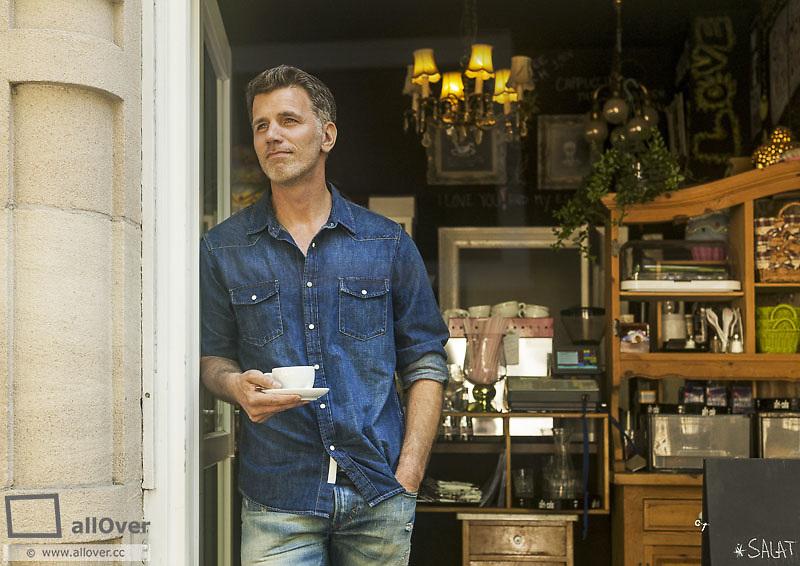 Mann steht in Ladeneingang, mit Kaffeetasse (model-released)