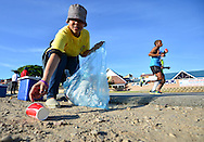 MOSSEL BAY, SOUTH AFRICA - SEPTEMBER 24: a lady manning the PetroSA water table picks up discarded water sachets and cups from the ground during the PetroSA Marathon finishing at Santos Caravan Park on September 24, 2016 in Mossel Bay, South Africa. (Photo by Roger Sedres/Gallo Images)
