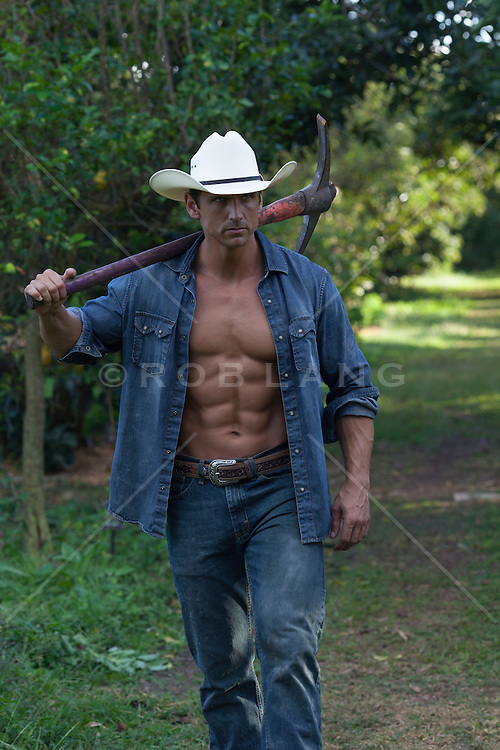 masculine muscular cowboy walking in a field<br /> carrying a pickaxe