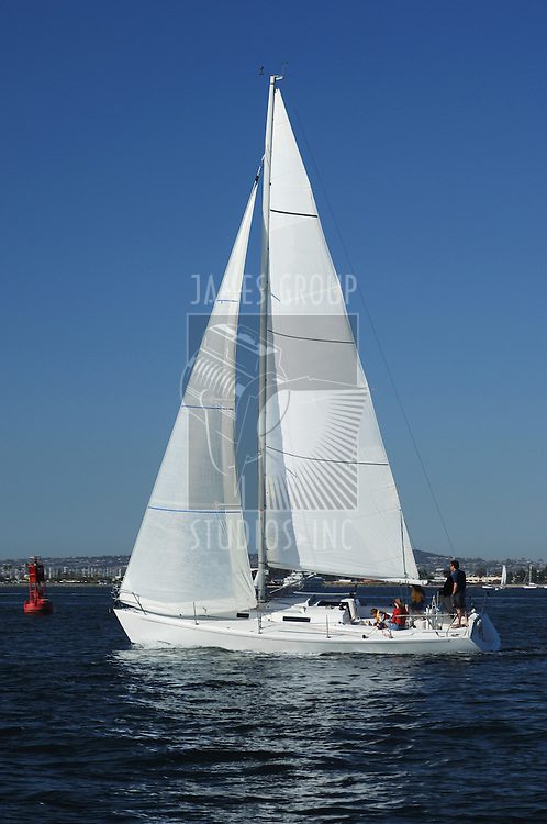 white sailboat with white sails in San Diego Bay on a clear day