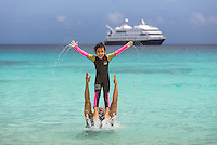 Father and daughter enjoying the water on their vacation at Gardner Bay on Espanola Island, Galapagos.
