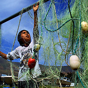 Grant Meanus, 10, seperates his uncle's fishing net set out for drying, he a member of the Celilo Indian tribe on their reservation in Celilo, Oregon.