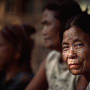A trio of women from the Laytu Chin tribe, whose female members traditionally had their faces tatooed, in their village near Mrauk U, Myanmar (Burma.)