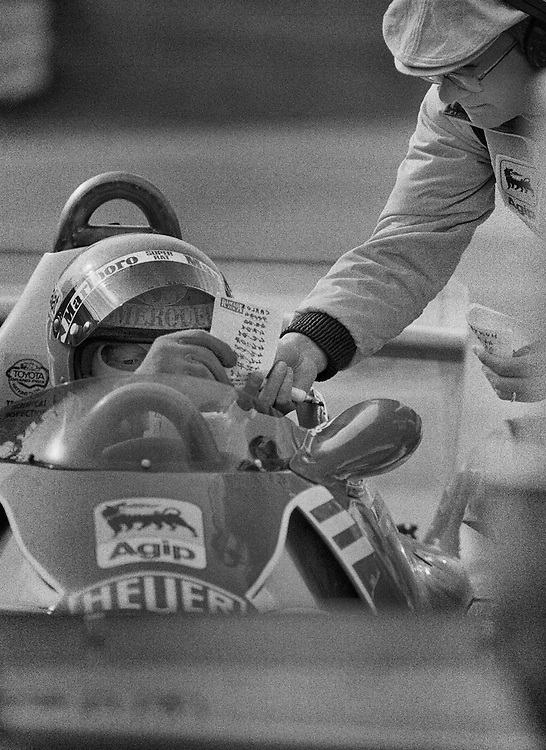 1975 World Champion Niki Lauda practices at the 1977 United States Grand Prix prior to winning his second World Championship.<br /> <br /> Here he compares his teammate, Carlos Reutemann's times to his own. In the Ferrari engineer's hand is another scrap on paper with Marlboro McLaren driver and Lauda's chief rival James Hunt.<br /> <br /> A year earlier, Lauda and Hunt had been involved in one of the most dramatic stories in the history of Formula One as they battled for the 1976 World Driver's Championship down to the final race in Japan. <br /> <br /> Lauda had lead the championship until his horrific accident that summer at the Nurburgring, were he received near fatal burns and inhaled toxic fumes...he had even received final rights of the Catholic Church. Hunt, in the meantime had won Germany and had closed up on Lauda's points lead. <br /> <br /> Miraculously, Lauda fought back and six weeks later, he returned to his Ferrari 312T at the Italian Grand Prix where he finished an incredible fourth. They arrived in Japan with Lauda ahead by three points. Hunt would win the title by a single point only after Lauda retired from the rain-soaked race because he felt conditions were too dangerous. The fire had destroyed Lauda's tear ducts and he couldn't see in the spray. <br />  <br /> This year, Hunt would win the 1977 United States Grand Prix, while Lauda would claim his second World Championship. He would add a third in 1984 with McLaren.