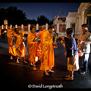 Buddhist Monks gather in Bangkok, Thailand to accept offerings and provide prayers to the faithful.