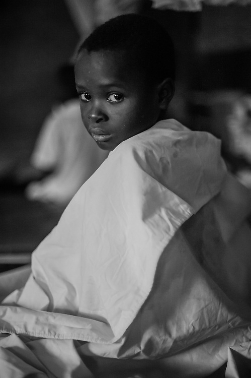A young boy silently watches everything that moves around him. He had been badly burned during a cooking accident. Mbuji-Mayi, DRC.