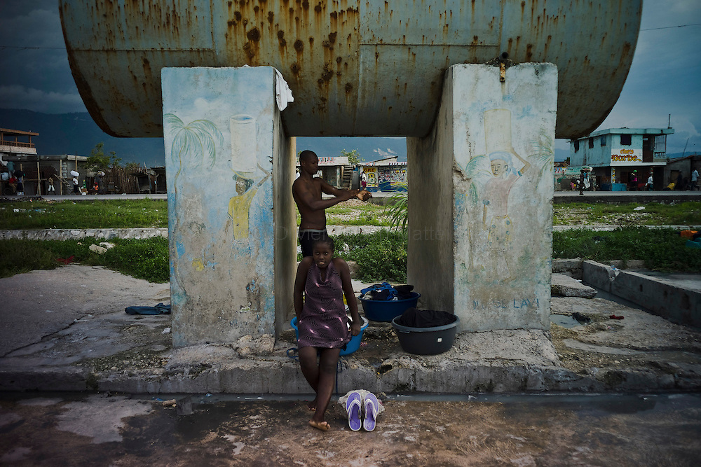 The number of cholera victims in Cité Soleil, a slum of Port-au-Prince, is increasing day by day exponentially, according to a doctor of Doctors Without Borders, essentially because of hygienic problems./// A man washes himself under a water tank in the slum of Cite Soleil in Port-au-Prince.