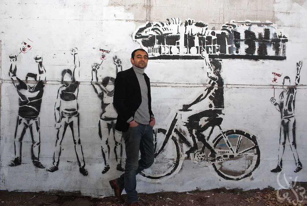 Egyptian social media artist Aalam Wassef poses for a portrait near revolutionary street graffiti January 11, 2012 in Cairo, Egypt.  (Photo by Scott Nelson)