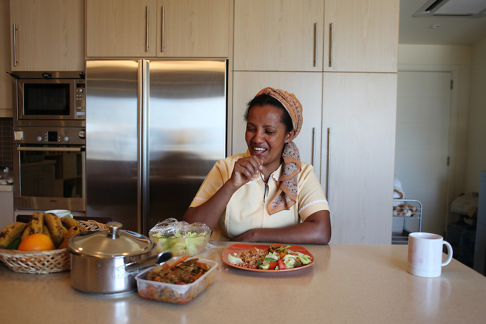 An Ethiopian woman takes a lunch break after cleaning the floors of her employer's home.