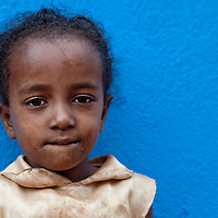 Young girl against a blue wall in Delo Mena, Ethiopia