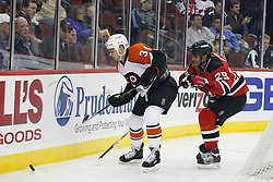 November 8, 2007; Newark, NJ, USA;   Philadelphia Flyers center Jim Dowd (34) and New Jersey Devils defenseman Johnny Oduya (29) battle for the loose puck behind the Devils goal during the third period at the Prudential Center in Newark, NJ.  The Devils won the game by a 4-1 score.
