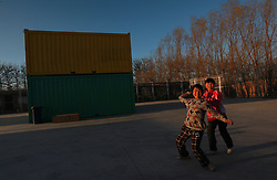 Migrant children play a game of throwing bags around a newly opened community centre built out of shipping containers by non-profit organisation Compassion for Migrant Children (CMC) in a migrant community in Beijing, China on 24 March 2011. CMC started the mobile community centre for migrant children and their families from containers custom made to fit as classrooms, computer labs, and offices. This is the first time the non-profit organisation is setting up a new container community centre to cater to the growing needs of migrant workers in the city who are often forced to move when the area they live in are redeveloped or demolished. The community centre will offer vocational training for youths, extracurricular activities for children, training for new mothers and family health
