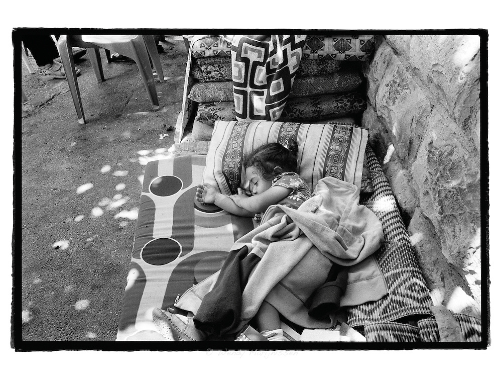 Forced to live on the streets, children of the al-Ghawi family are taking an afternoon nap on the matrassess on the street opposite their fomer home.