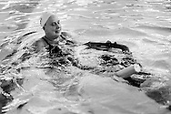 Jane Katz, a professor at at the John Jay College, helps a student as she  leads a swim class for incarcerated youths at the school's pool in New York, July 17, 2010. Keith Bedford for the New York Times