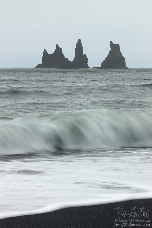Atlantic Ocean waves crash on a black sand beach overlooking Reynisdrangar, the Troll Rocks near Vík, Iceland. According to Icelandic legend, the rocks are the remnants of trolls that were out fishing too late. The legend says trolls will turn to stone if they're exposed to daylight.