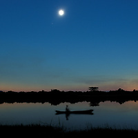 Africa, Zambia, Lukata, Village man paddles dugout canoe on lake during total solar eclipse on June 21, 2001