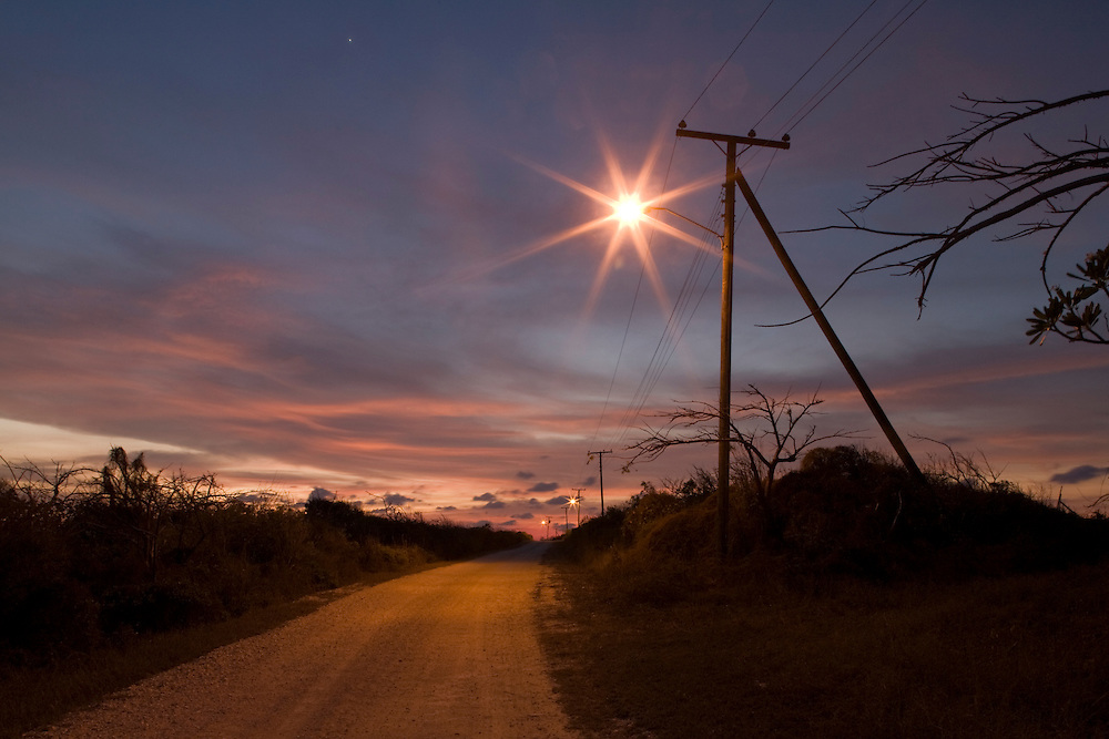 Cayman Islands, Little Cayman Island, Street light and telephone pole along country road at dusk