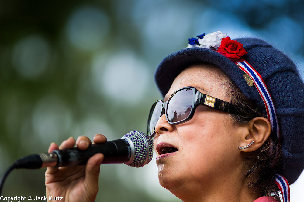 "15 JUNE 2014 - BANGKOK, THAILAND: A woman wearing a Thai patriotic headband sings folk songs on a stage during a ""Return Happiness to Thais"" party in Lumpini Park in Bangkok. The Thai military junta, formally called the National Council for Peace and Order (NCPO), is sponsoring a series of events throughout Thailand to restore ""Happiness to Thais."" The events feature live music, dancing girls, military and police choirs, health screenings and free food.    PHOTO BY JACK KURTZ"