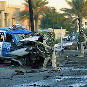 19 November 2004.Baghdad, Iraq..Car bomb targets police convoy...Iraqi security forces, US soldiers and rescue workers at the scene of a suicide car bomb, Friday 19th October in Baghdad, Iraq. The bombers target was a police convoy, the attack killed 5 wounding a futher 10 and damaging nearby houses. The casualties were rushed to hospital first then bodies were removed from destroyed vehicles.