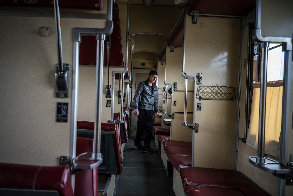 Bogdan Ryzhkov, 17, who fled fighting in the heavily-contested town of Debaltseve, inside the train car where he is living with other members of his extended family at the train station on Monday, February 9, 2015 in Slovyansk, Ukraine.