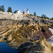 A unique landscape of beautifully striped bedrock descends from Pemaquid Light to the Atlantic Ocean. Pemaquid Point Lighthouse was built in 1835 and commemorated on Maine's state quarter (released 2003). Visit Lighthouse Park at the tip of Pemaquid Neck in New Harbor, near Bristol, Lincoln County, Maine, USA. From Damariscotta on bustling US Highway 1, drive 15 miles south on Maine Route 130 to the park. The keeper's house (built 1857) is now the Fishermen's Museum at Pemaquid. Geologic history: Silurian Period sediments laid down 430 million years ago were metamorphosed underground into a gneiss 360-415 million years ago, and intruded by molten rock which cooled slowly, creating the park's exposed metamorphic gray rocks with dikes of harder, white igneous rock. Underground heat and pressure tortured and folded the rock layers into the striking patterns that are now pounded and polished by the sea and rough weather. The panorama was stitched from 5 overlapping photos.