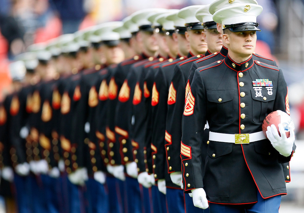 A group of U.S. Marines in dress uniform, one carrying a football leave the field before the NFL football game in Denver September 14, 2008. The Marines were part of the pre-game ceremonies. REUTERS/Rick Wilking (UNITED STATES)