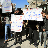 Demonstrators march for regime change whilst holding placards in the town of Al Janoudiyah, Syria.