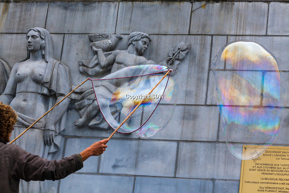 Brussels 2012 6 Mai. Big soap bubbles are blown by a street artist in the centre of Brussel, on the art-mountain, Kunstberg. A monument displaying the naked breasts of a woman, and an angel and pigeon form the background,being a hommage to the fallen jews and Belgians in the 2nd worldwar. The copper plaque shows the names of Andre Flahaut and former prime minister of Belgium Guy Verhofstadt, who attended the opening of the monument.