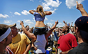 To the raucous cheers of those surrounding her, a young woman bares herself to the crowded Pinlico Race Course infield. The infield during Preakness Day is a world unto itself, separated by fences —and police — from the other  fans attending the second jewel in the Triple Crown.