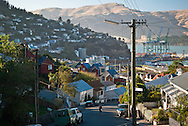 Elevated view of a man crossing Hawkhurst Road in the port town of Lyttelton, Canterbury, New Zealand, looking out over the township and distant mountain landscape