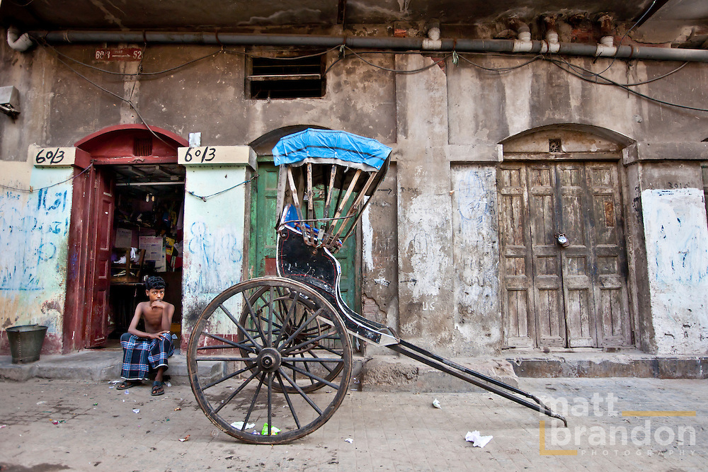 Parked outside a residence, this rickshaw awaits its puller.