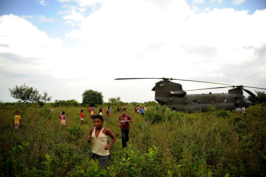 Local children from the village of Wawina, Honduras, scatter before the engines of a CH-47 Chinook fire up and take the U.S. military members from the Joint Task Force-Bravo Medical Element back to Soto Cano Air Base. — © /