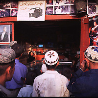 """HOTAn , 3 october 2001: young Uighur men watch a video at a local store in Hotan.Uighurs have their own idols and Chinese efforts to """"educate"""" Uighurs have mostly failed.KASHGAR, SEPTEMBER 29 : Uighur muslim women walk in the bazaar in Kashgar.  Uighur muslims in China's western Xinjiang province mostly stick to islamic lifestyles due to their proximity to Afghanistan & Pakistan . Today, 47 percent of Xinjiang is Uighur and 41 percent is Han. Smaller groups of other Turkic Muslims, including Kyrgyz, Kazakhs, Tajiks and Uzbeks, make up the remainder of the population ..The government maintains tight control over Uighur culture.All mosques are required to register with the government. In 2001, authorities called in 8,000 imams for special training on the Communist Party's ethnic and religious policies. In 2002, Xinjiang's top university eliminated all instruction in the Uighur language. ... . .   . . .  . (photo by: katharina hesse/Grazia Neri)."""