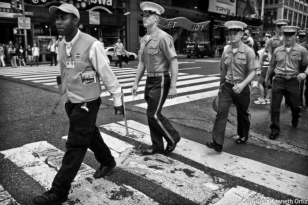 A group of Marines being lead by a Grey line bus vendor crossing 42nd Street in Time Square during Fleet Week.