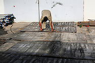 A Libyan rebel prepares steel plates for cutting as it it will be used to armour technical trucks in a arsenal workshop. Outmatched in weaponry by loyalist forces, rebels relies on captured heavy machine guns, 23mm AA cannon and recoilless 106mm M40 rifle. Pick up trucks are painted black, guns weld on and  armored with steel plates. Creativity and resolve are trademarks of Misrata high spirit. 18 May 2011.
