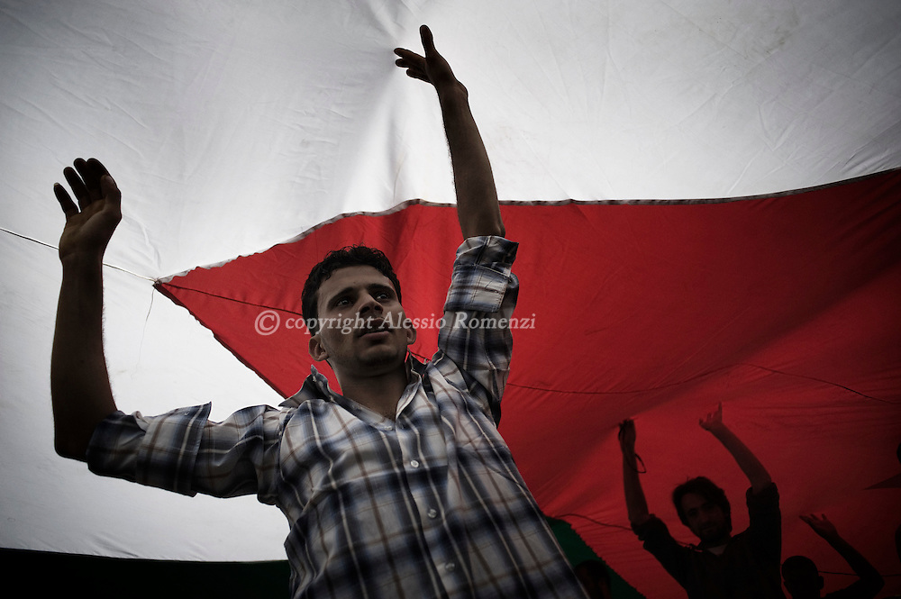 JORDAN, Amman : Jordanian demonstrators dance under a giant flag during a demonstration in the capital Amman on April 1, 2011, calling for reforms, a week after clashes between them and government supporters killed a man and injured 160. ALESSIO ROMENZI
